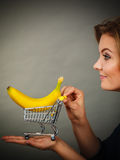 Woman holding shopping cart with banana inside. Buying healthy food, vegetarian, gluten free, vegan products. Woman holding shopping cart with banana inside Stock Photos