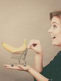 Woman holding shopping cart with banana inside. Buying healthy food, vegetarian, gluten free, vegan products. Woman holding shopping cart with banana inside Royalty Free Stock Photos