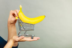 Woman holding shopping cart with banana inside. Buying healthy food, vegetarian, gluten free, vegan products. Woman holding shopping cart with banana inside Stock Photography