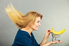 Woman holding shopping cart with banana inside royalty free stock photography