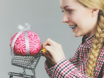 Woman holding shopping cart with brain Royalty Free Stock Photography