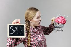 Woman holding shopping cart with brain Royalty Free Stock Images