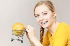 Woman holding shopping cart with bread. Buying gluten food products concept. Woman holding shopping cart trolley with small piece of bread bun Royalty Free Stock Photo