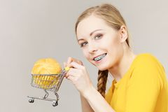 Woman holding shopping cart with bread. Buying gluten food products concept. Woman holding shopping cart trolley with small piece of bread bun Stock Photo