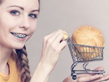 Woman holding shopping cart with bread. Buying gluten food products concept. Woman holding shopping cart trolley with small piece of bread bun Stock Image