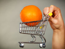 Woman holding shopping cart with orange inside Royalty Free Stock Images