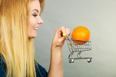 Woman holding shopping cart with orange inside. Buying healthy food, vegetarian, gluten free, vegan products. Woman holding shopping cart with orange inside Stock Images