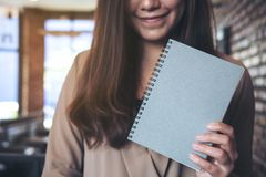 A woman holding and showing blank grey notebook in office. Closeup image of a woman holding and showing blank grey notebook in office Stock Photo