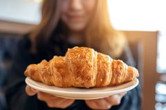 Woman holding and showing a dish of fresh croissant. An asian woman holding and showing a dish of fresh croissant stock photography