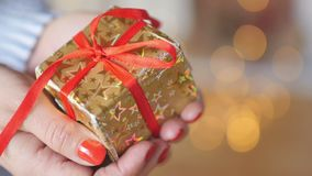 Woman holding showing gift. Close up gift, Woman holding showing gift in golden box with red ribbon. Female hands giving present stock video