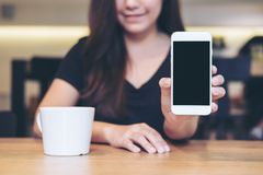 Woman holding and showing white mobile phone with blank black screen. Mockup image of an Asian beautiful woman holding and showing white mobile phone with blank Royalty Free Stock Photos