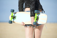 Woman holding Skateboard Stock Images