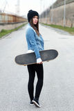 Woman holding skateboard Royalty Free Stock Photography