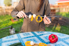 Woman holding skewers of fresh vegetables Stock Photo