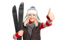 Woman holding skis and giving thumb up Royalty Free Stock Photo