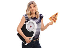 Woman holding slice of pizza and weight scale Stock Photos