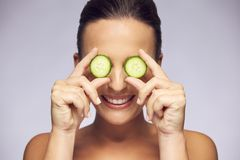 Woman holding slices of cucumber over eyes Royalty Free Stock Images