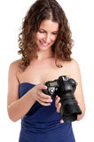 Woman Looking at a Camera. Woman holding an SLR camera and looking at the picture she took, isolated in white Royalty Free Stock Photo