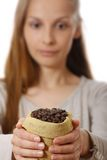 Woman holding a small bag of coffee beans Royalty Free Stock Photo