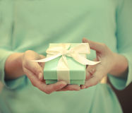 Woman holding a small blue box with a white ribbon. In her hands Stock Photography