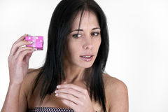Woman holding small box up to her ear. Woman holding small pink box up to her ear Royalty Free Stock Image