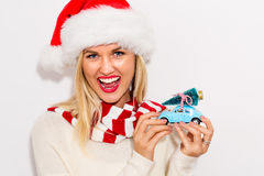 Woman holding small car with Christmas tree Stock Images
