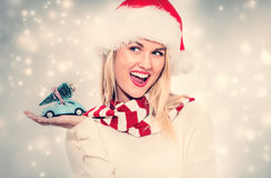 Woman holding small car with Christmas tree Royalty Free Stock Images