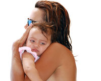 Woman holding small child. A profile of a woman, wet from the swimming pool, holding a little girl in her arms Royalty Free Stock Photo