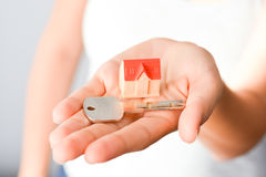 Woman holding a small model house and a key suggesting house acquisition or rental. Close-up of woman`s hands holding a small model house and a key suggesting Stock Image