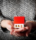 Woman holding a small new house in her hands Stock Image