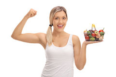 Woman holding a small shopping basket and flexing her bicep Royalty Free Stock Image