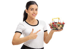 Woman holding a small shopping basket and pointing Stock Photos