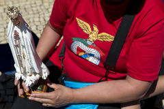 Woman holding a small statue of the Virgin Mary and wearing a Benfica shirt  at the Sanctuary of Fatima during the celebrations of. Fatima, Portugal - May 13 Stock Image