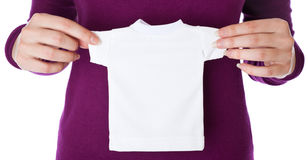 A woman is holding a small T-shirt in her hands Royalty Free Stock Photography