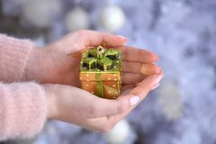 Woman holding small yellow present box in hands Royalty Free Stock Photography