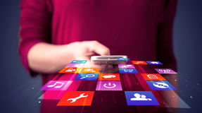Woman holding smart phone with colorful application icons Royalty Free Stock Photo