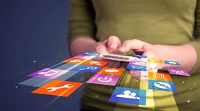 Woman holding smart phone with colorful application icons royalty free stock images