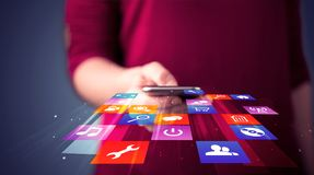 Woman holding smart phone with colorful application icons stock image