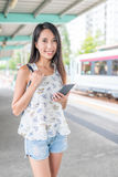 Woman holding smart phone on light rail train station in Hong Ko. Ng ,asian young woman Stock Image