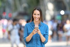 Woman holding smart phone looks at camera Stock Photography