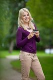 Woman Holding Smart Phone In Park Stock Images