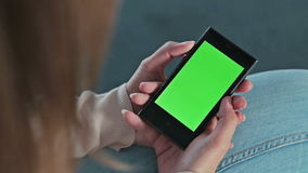 Woman holding smart phone phone with green screen stock video footage