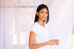 Woman holding smart phone. Smiling indian woman holding smart phone at home Royalty Free Stock Photo