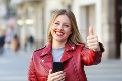 Woman holding smart phone with thumb up on the street Royalty Free Stock Images