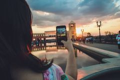 Woman Holding Smartphone Capturing Sunset Royalty Free Stock Photography