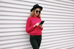 Woman holding smartphone in colorful pink knitted sweater. Fashion, technology and people concept - woman holding smartphone in colorful pink knitted sweater stock image
