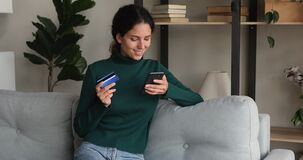 Woman holding smartphone and credit card makes secure payment