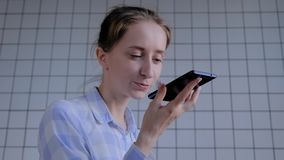 Woman holding smartphone and using voice recognition function
