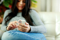 Woman holding smartphone at home. Focus on phone. Royalty Free Stock Photography
