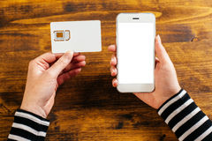 Woman holding smartphone and new SIM card Royalty Free Stock Photos